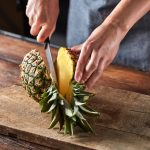 The girl's hand with a knife cuts a tropical fruit pineapple on a board on a wooden brown table